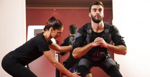 personal trainer helping man train with ems suit
