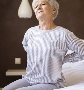 elderly lady with a back pain sitting on the edge of a bed
