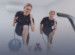 man and woman smiling whilst training with ems