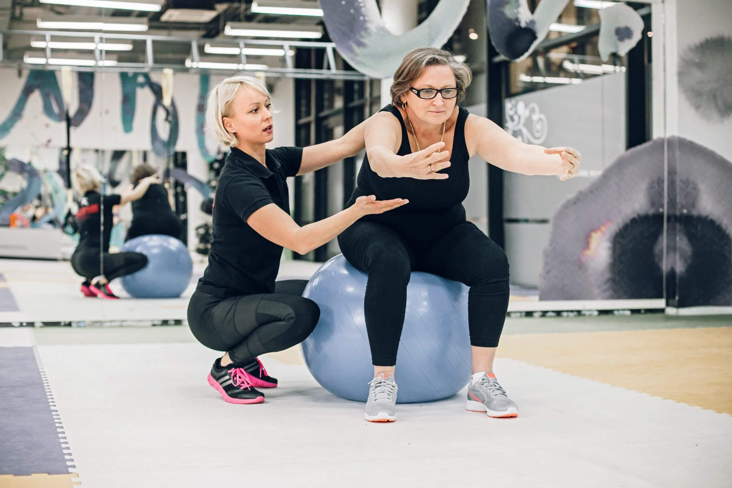 exercising with a personal trainer on a fitness ball