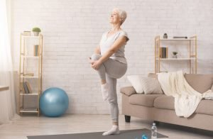 elderly lady doing yoga at home on a yoga mat